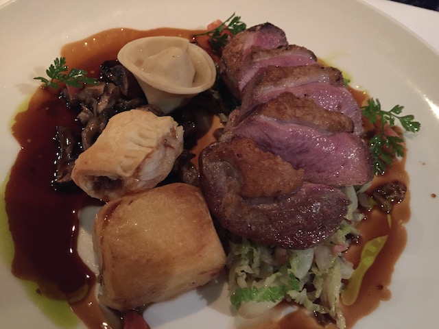 Gressingham duck breast with confit leg ravioli, duck sausage roll, fondant potato, wild mushrooms, savoy cabbage with bacon and jus