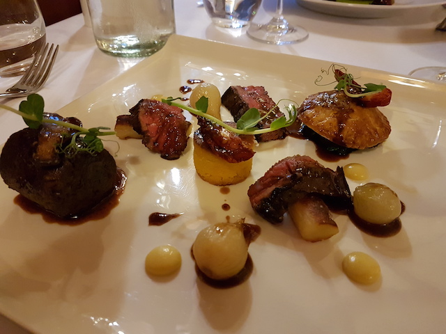 A plate showing trio of beef; bavette, cheek and oxtail, sweetcorn purée and burnt onion gel