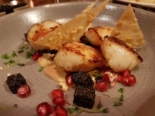 Plate of food at Taisteal in Edinburgh showing Pan Fried Scallops with Satay Sauce, Black Pudding Pomegranate