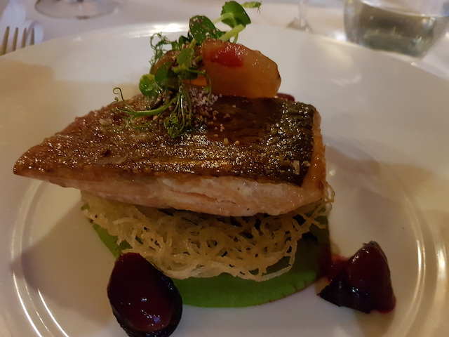 Plate with Earl Grey smoked trout, crispy rice noodles, asparagus, bitter raspberry and beetroot