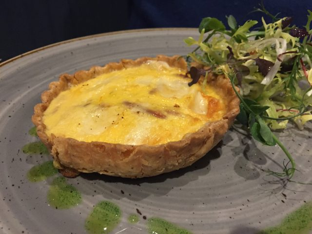 Plate showing Smoked cheddar tart with duck egg, caramelised red onion and Arran smoked cheddar