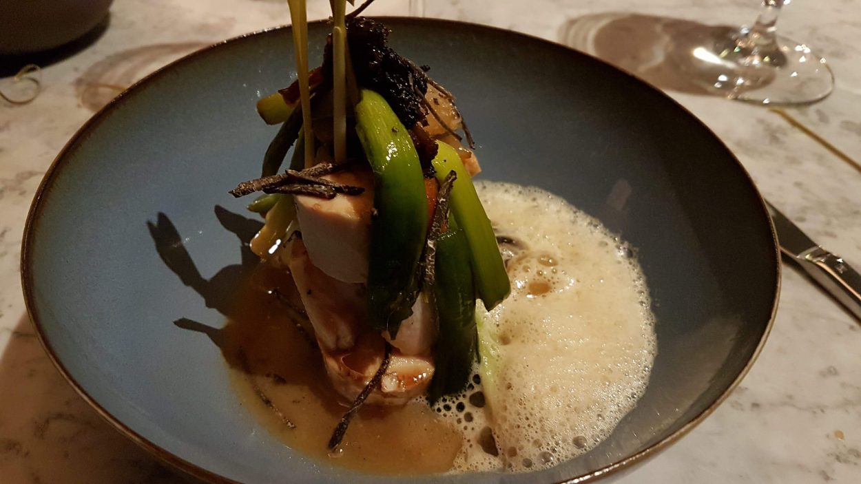 Plate showing poached and roasted free-range chicken, leeks, morel nage